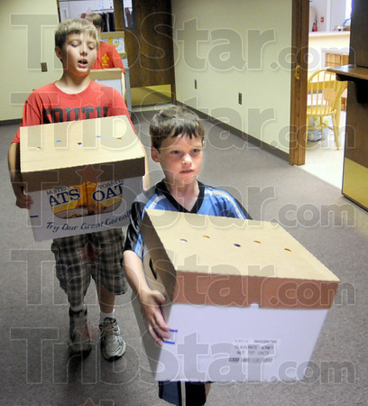 Helpers: Brandon Chamberlain (L) and Scott Thurston carry boxes of food into the Salvation Army food pantry Friday morning.