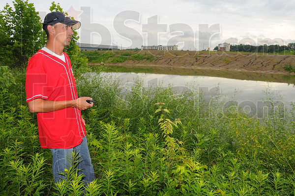 Tribune-Star/Jim Avelis<br /> Looking: Adam Garrett of Columbus looks near a wooded area around retention ponds just west of the Value Place extended stay motel where Morgan Johnsonm was last seen.