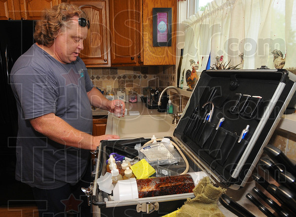 Tribune-Star/Jim Avelis<br /> Looking for answers: Mike Byrd collects water from the kitchen tap in Gwen Mildazis' Terre Town home Friday evening.
