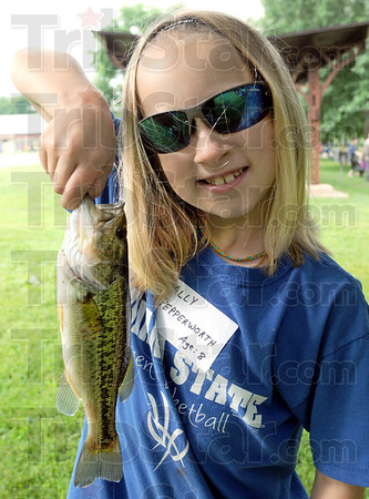 Bass master: Eight-year-old Ally Pepperworth proudly displays her bass catch during Saturday's Fishing Rodeo at Dobbs Park.