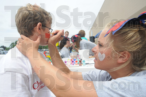 Tribune-Star/Rachel Keyes<br /> Helping out kids: Mitchell Abbey gets his face painted by Terre Haute North cheerleader Christina Jones.