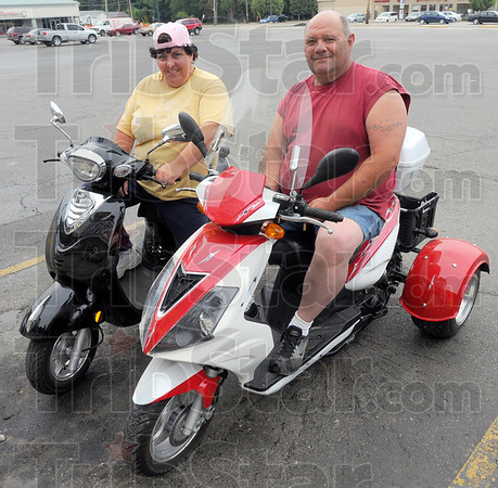 Tribune-Star/Jim Avelis<br /> Cheap ride: Melony and Scott Martin said the price of gas is the reason they choose mopeds as their mode of transportation. They are glad to see the new laws regarding registration, hoping it will help deter theft.