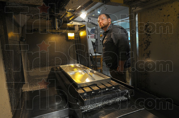 Tribune-Star/Jim Avelis<br /> Form follows function: Flying S Inc. manufacturing engineer Peter Bowman at one of the machines used to make the forms that will cast the carbon fiber components.