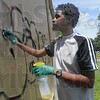Tribune-Star/Rachel Keyes<br /> Elbow grease: Shaquille Towns scrubs off some graffiti off the side of Family Dollar on Popular Street as part of a community service project at the NAACP Youth Summit Saturday afternoon.