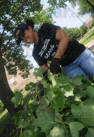 Tribune-Star/Rachel Keyes<br /> Unwanted brush: Indiana State NAACP Youth and College President Kayla Davis spends some time clean up limbs in the court house lawn as part of a community service project at the NAACP Youth Summit Saturday afternoon.
