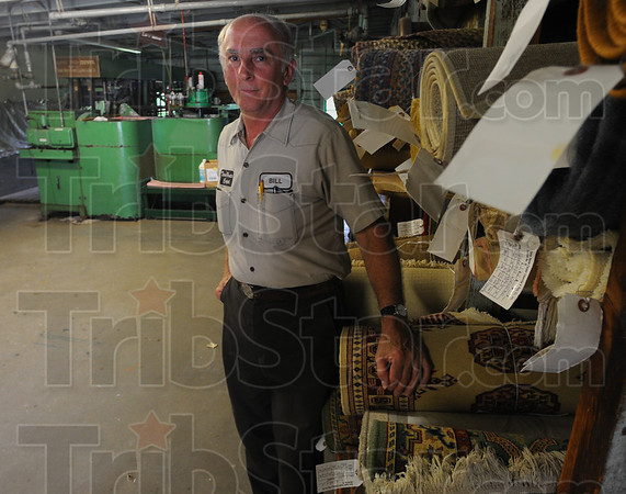 Tribune-Star/Jim Avelis<br /> Ready to go: Bill Siebenmorgan stands by cleaned area rugs ready for delivery back to customers. The rugs are cleaned then dried in batches since it takes a lot to get the machinery for both cleaning and drying going.
