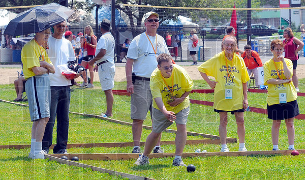 Tribune-Star/Jim Avelis<br /> Bowl for gold: Vigo County Special Olympians competed in the bocce ball tournament on a hot Saturday afternoon. Competitors in the yellow shirts are:  Eldon Watts, Jason Whitt bowling, Judy Clark and Tammy Good.