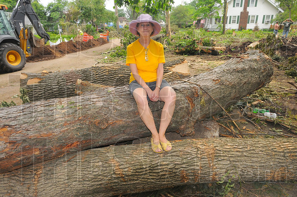 Stephanie Salter sitting on tree trunks along the tree row in front of her northside home.