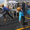 Tribune-Star/Jim Avelis<br /> You're it: Isaac Fisher and his brother Christian play a game of tag early Saturday morning at the farmers' market.