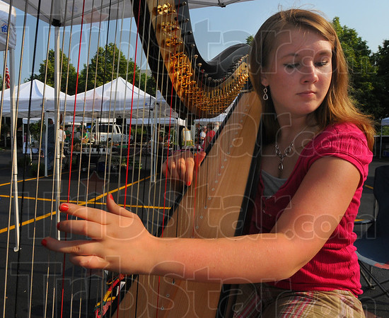 Tribune-Star/Jim Avelis<br /> Ambiance: Madison Muncie of Cory and a student in Indiana Universities' pre-harp program, provided background music on the opening day of this years' farmers' market.