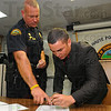 Tribune-Star/Jim Avelis<br /> Details: Terre Haute police chief John Plasse directs new officer John Goldner where to sign his name on his first paperwork as a city policeman.