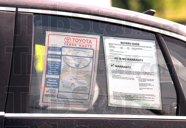 Warranty: A new vehicle involved in an accident is towed from the scene with the warranty visible on the window sticker.