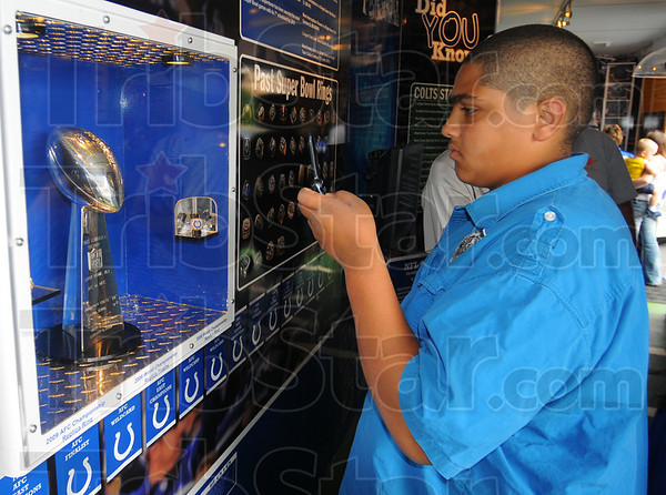 """Tribune-Star/Jim Avelis<br /> Things to come: Joseph Hall, a Terre Haute North student, snaps a picture of the Colt's Super Bowl trophy Wednesday evening during the """"Make it Personal"""" tour."""