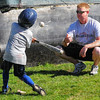 Tribune-Star/Jim Avelis<br /> Training: Mekhi Higgins practices his swing with help from assistant coach Josh Deveau at the Terre Town baseball park Tuesday evening.