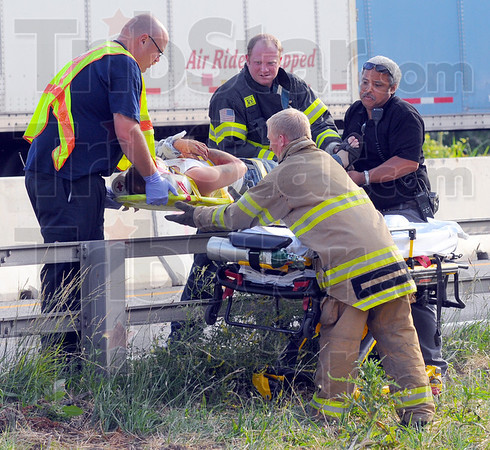 Tribune-Star/Jim Avelis<br /> Helping hands: Emergency responders lift onto a gurney one of the persons injured in the multi-semi crash on I-70 Monday night. Three persons were taken to hospitals and seven others were treated at the scene.