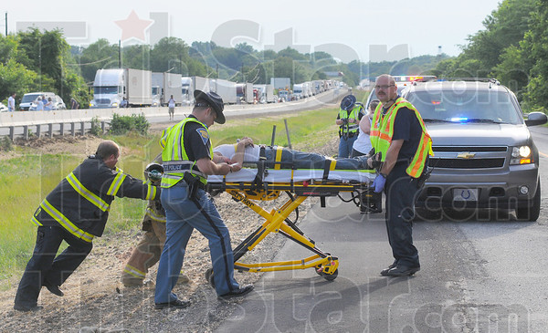 Tribune-Star/Jim Avelis<br /> Wreck rescue: Sugar Creek volunteers and police officers aid a person injured in a chain-reaction accident Monday evening on I-70 near the 4-mile marker in western Vigo County.