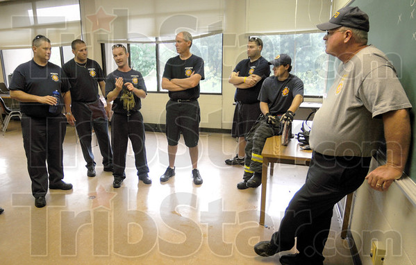 """Classroom: Members of the Terre Haute fire department gather at the end of Monday's training exercise for techniques of fighting """"high rise"""" fires. At right is battalion Chief Bob Kiefner."""