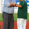 Tribune-Star/Jim Avelis<br /> Let's talk: Base umpire Scott Mason talks with Quincy coach Chris Martin following a close call in the Gems' game with the Rex Monday evening.