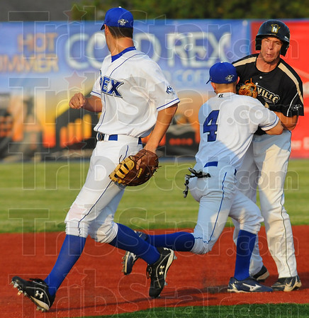 Tribune-Star/Jim Avelis<br /> Stopped cold: Rex second baseman Cameron Fagg(4) tags an Outlaw baserunner out on a rundown between first and second base.