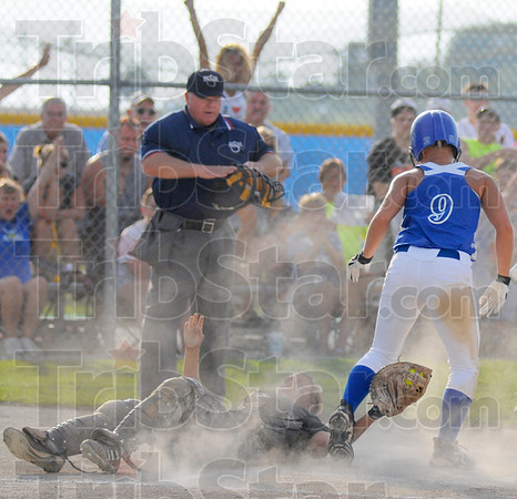 Tribune-Star/Jim Avelis<br /> Safe at home: Rockville baserunner Lindsey Greene(9) stands over Frontier catcher Kattie Lee after sliding safe into home.