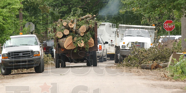 Tribune-Star/Jim Avelis<br /> Another load: A tree service dump truck wends its way through northside streets, taking storm debris away to be ground into mulch or fuel.