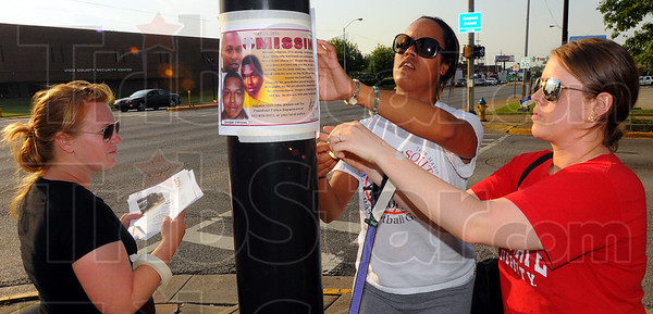 Tribune-Star/Jim Avelis<br /> Alert: Christina Fiddler, Amber Stewart and Melissa Humphrey tape posters to a downtown utility pole to help spread awareness of the missing Morgan Johnson.