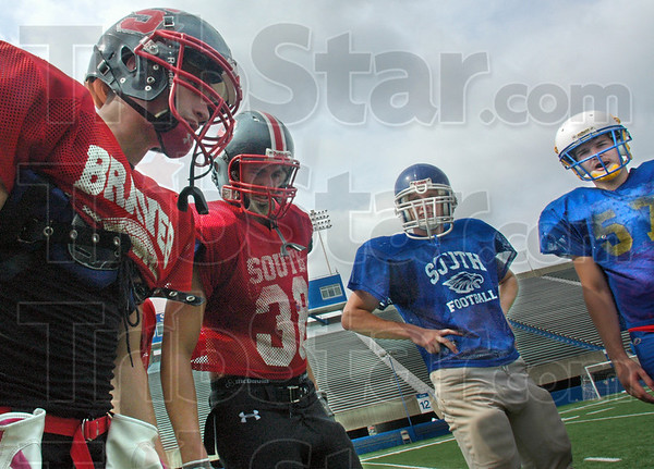 Play call: Terre Haute South quarterback Kevin Bracken (L)calls a play in the huddle during Tuesday's All-Star football practice at Memorial Stadium.