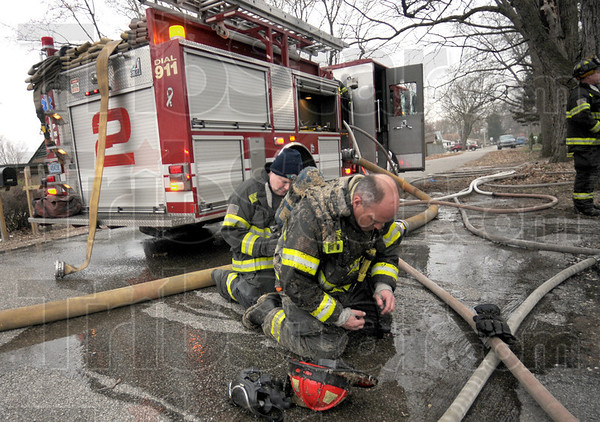 Change: Terre Haute fire department Captain John Gardner gets his air tank changed at the scene of a house fire Thursday morning.
