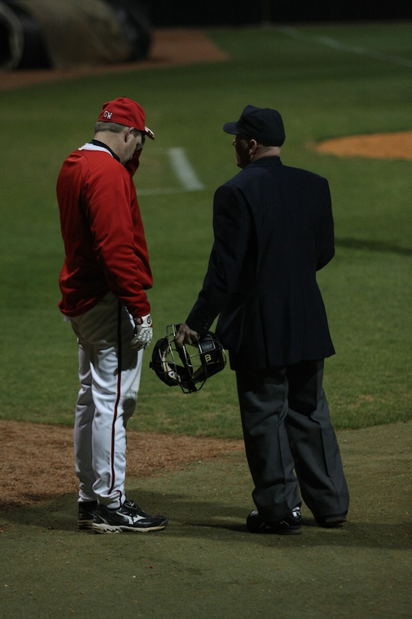 Coach, frustrated with a call saying the High Point batter was hit at the plate, discusses the issue with the umpire.
