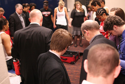 The team gathers for prayer after the game