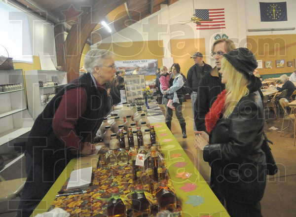 Tribune-Star/Rachel Keyes<br /> A history of syrup: Fifth Generation maple syrup maker Rebecca Pefley (left) talks with customers Jim Garrison (middle) and Marian Koenig (right) who drove in from Lafayette, IN for the festival.