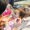 Tribune-Star/Rachel Keyes<br /> Blue is my color: Indiana State Cheerleader Paige Richards (left) paints the letters ISU in blue on the cheek of eighteen-month-old Ana Sosia Anderson (Middle) as she sits still her mother Marisol Anderson's (right) lap.