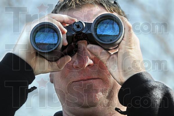 Scanning: Marty Jones uses binoculars to scan the horizon in the J. I. Case Wetlands Saturday morning.