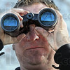Scanning: Marty Jones uses binoculars to scan the horizon in the J. I. Case Wetlands Saturday morning.