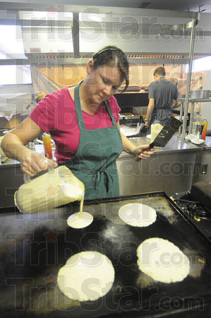 Tribune-Star/Rachel Keyes<br /> Cook it up: 4-H Volunteer Karen Eldridge pours some pancake batter on the griddle for the Maple Syrup Festival's pancake breakfast.