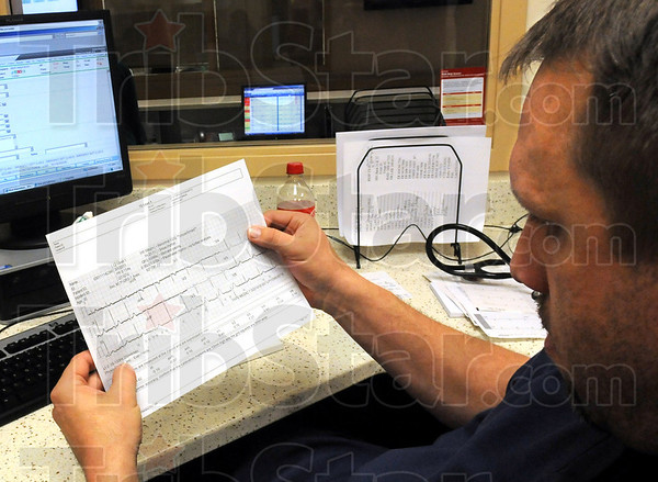 Information: Union Hospital emergency room Dr. Eric Heath reads EKG information transmitted by a Terre Haute Fire Department ambulance Tuesday afternoon.