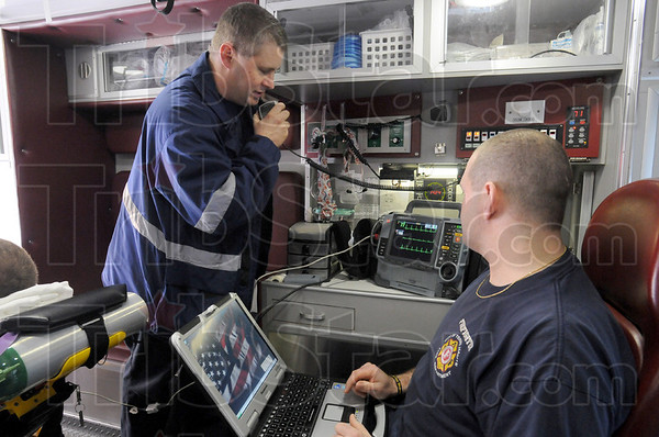 Testing: Paramedic Jim Kempf calls the Union Hospital emergency room to let them know he's sending information from a heart monitor for testing. At right is Kempf's partner B.J. Barnes.