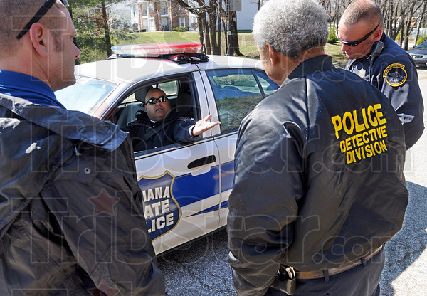 Information: Indiana State Police trooper Todd Miles gets information from Terre Haute police Chief John Plasse (R), Detective Lt. Ed Tompkins (center) and Sgt. Jason Czupryn (L) Friday afternoon at the scene of the incident.