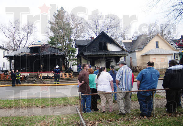 Tribune-Star/Rachel Keyes<br /> Destroyed: People stand and watch as firefighters clean up after a fire blazed through two houses on 24th and Liberty street Friday morning.