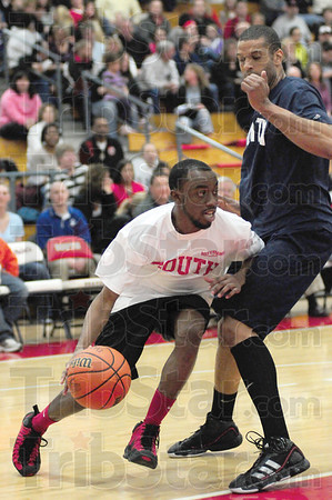 Tribune-Star/Rachel Keyes<br /> To the basket: Terre Haute South's Dominque Norton tries to take it the basket against Terre Haute North's Bryan Reed in alumni action Friday night.