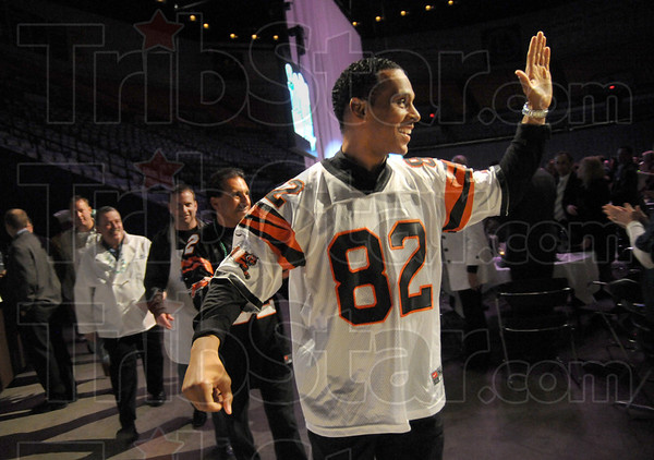 Grand Marshal: Former Cincinnati Bengal Tony McGee waves to the packed house as he leads the 100 Men Who Cook to their places Saturday night.
