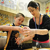 Tribune-Star/Rachel Keyes<br /> Seeds of growth: Second grader Dylan Dickens (left) plants seeds in a glove with help from Indiana State student Danielle Schuster (right).
