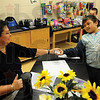 Tribune-Star/Rachel Keyes<br /> I earned it: Vigo County School Counselor Karla West (left) takes a paycheck from Franklin Elementary student Jonathan Olson (right) who as picked out a basketball with his earnings. Jonathan has been saving for three weeks to earn enough franks to make his purchase. Students earn a frank a week for perfect attendance.