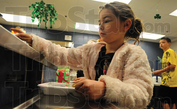 Tribune-Star/Rachel Keyes<br /> Brain food: First grader Brionna Shafer punches in her Id number as she picks up she breakfast early Monday morning at Franklin Elementary School.