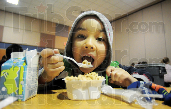 Tribune-Star/Rachel Keyes<br /> Feed the mind: Kindergartner Ethan Cooper gobbles down his breakfast before heading off to class early Monday morning at Franklin Elementary.