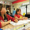 Tribune-Star/Rachel Keyes<br /> Lessons learned: Third grader Hailey Smith takes notes of the projector in class Monday morning.