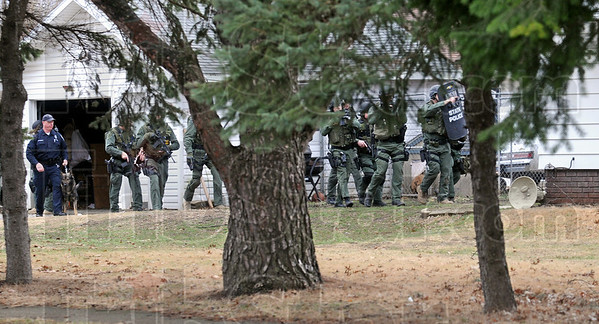 On the move: Members of the Indiana State Police special response team move on a house where they believed a homicide suspect was holed-up Wednesday afternoon.