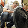 Wheel man: Rose-Hulman student Andrew Bomar works on the frame and wheel of the human powered vehicle Wednesday evening on the Rose campus.