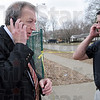 Hold the busses: Vigo County School Corporation representative Mick Newport (L) talks with school officials calling for a stop to student pick-up at Woodrow Wilson because of a police action near the school. Terre Haute police detective Troy Pesavento gets instruction at right.