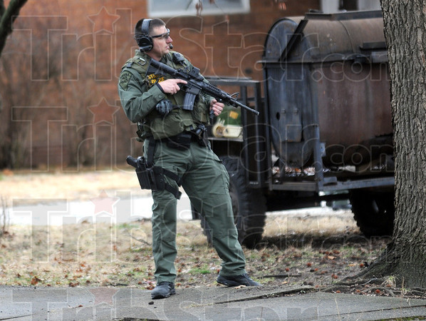 Cover: An Indiana State Police special response team member takes cover behind a tree as he keeps watch on a residence near 22nd and Poplar Streets Wednesday afternoon.